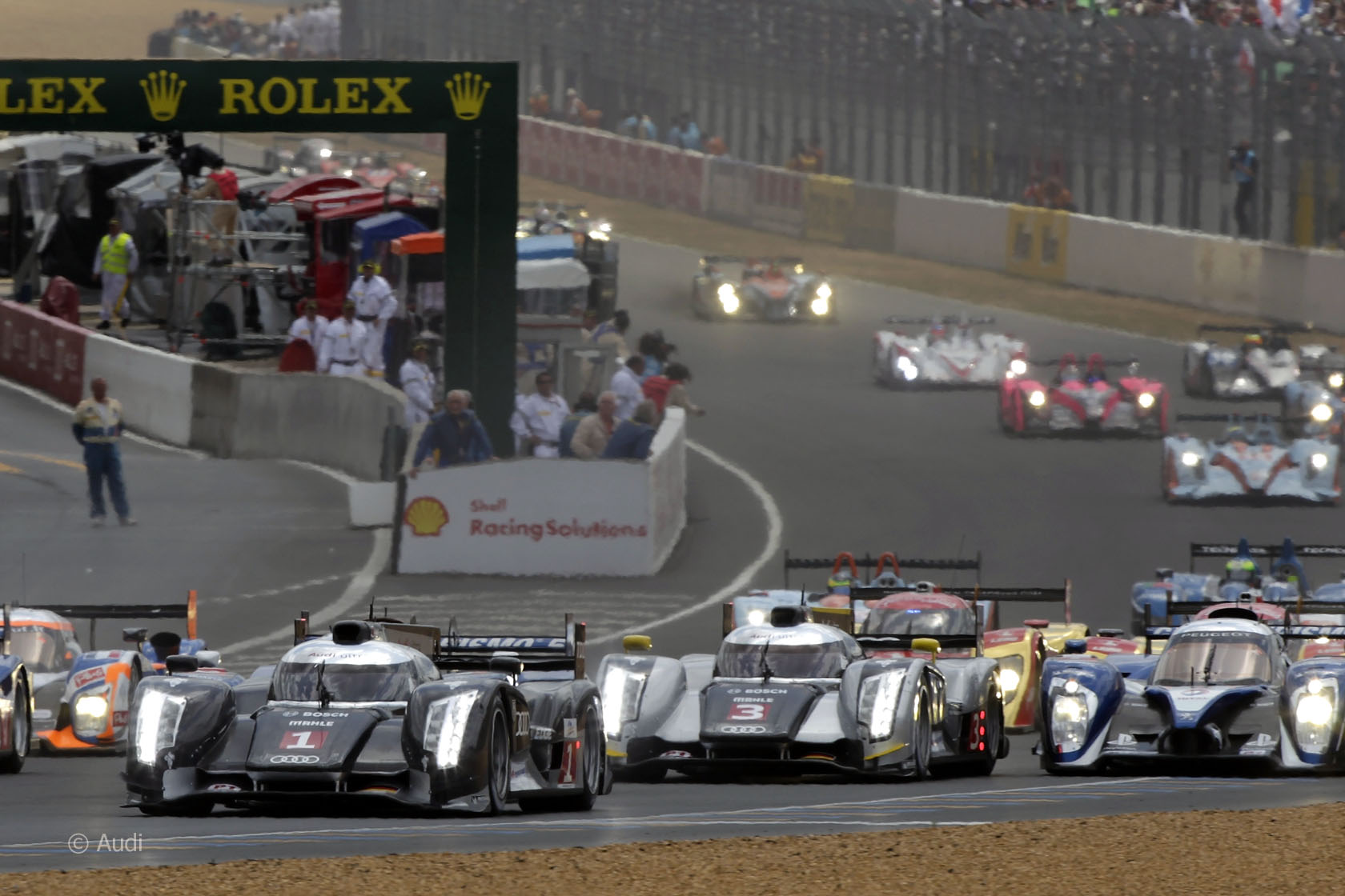 Se largan las 24 Horas de 2011 y el grupo de punta lo integran los Peugeot y los Audi. Entre estos últimos, aquí se ve a los números 1 y 3 que serían los que sufrirían tremendos accidentes raleando al grupo alemán y dejando al nº2 defendiendo los colores de la marca.