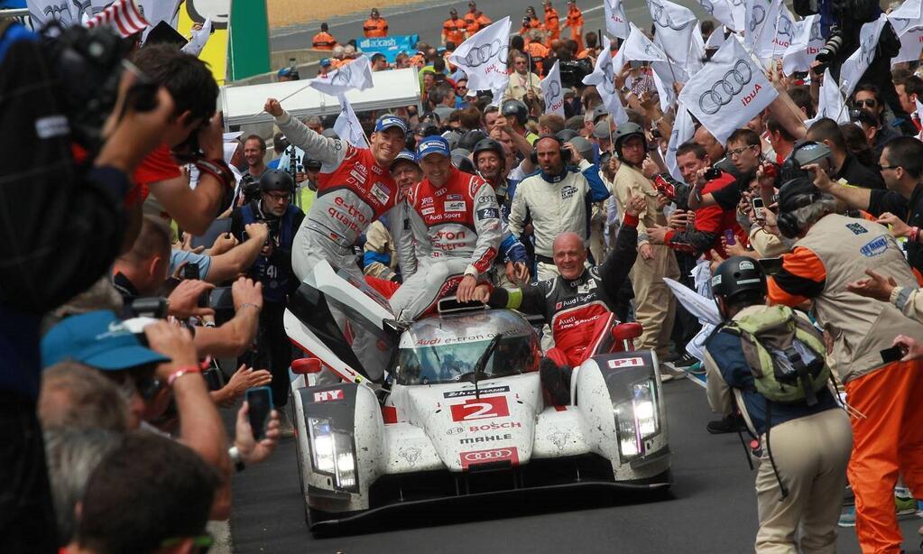 Rumbo al ?círculo de la gloria?, al pie del podio de Le Mans, avanza el Audi R18 e-tron quattro vencedor, con gran parte de los protagonistas sobre su sufrida estructura, los pilotos y el Dr.Ulrich, máximo responsable del equipo alemán?