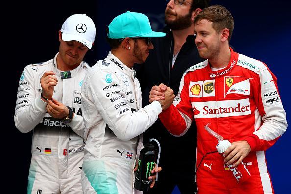 Hamilton y Vettel se congratulan con un distraído Rosberg atrás...